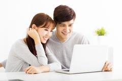 Jeunes couples heureux regardant l'ordinateur portatif Photographie stock libre de droits