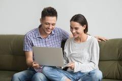 Jeunes couples heureux riant tout en faisant l'appel visuel sur l'ordinateur portable Images libres de droits