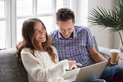 Jeunes couples heureux riant visuel drôle de observation en ligne sur l'ordinateur portable Photos stock
