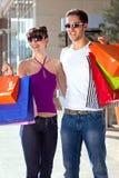 Jeunes ajouter gais aux sacs à provisions colorés Photographie stock