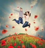 Jeunes couples heureux sautant dans le domaine de pavots Image stock