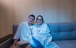 Jeunes couples heureux se blottissant vers le haut de la télévision de observation et de rire Image stock