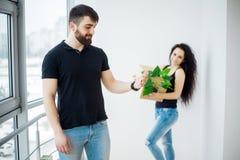 Jeunes couples heureux se déplaçant la nouvelle maison déballant des boîtes photos stock