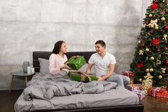 Jeunes couples heureux se donnant des présents tout en se reposant sur t Photographie stock libre de droits