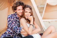 Jeunes couples heureux se reposant dans le tipi sur la plage Image libre de droits