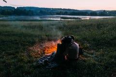 Jeunes couples heureux se reposant de retour sur le plaid embrassant par le feu la nuit Fille en guirlande Images stock