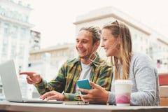Jeunes couples heureux se reposant en café avec l'ordinateur portable et discutant des plans ensemble Image stock