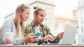 Jeunes couples heureux se reposant en café avec l'ordinateur portable et discutant des plans ensemble, homme étonné regardant l'é Photo stock