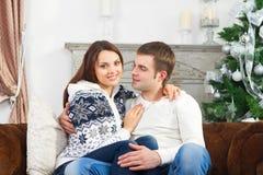 Jeunes couples heureux se reposant par l'arbre de Cristmas Photographie stock