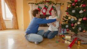 Jeunes couples heureux se reposant sur le plancher au salon et ayant l'amusement tout en décorant l'arbre de Noël banque de vidéos