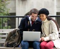 Jeunes couples heureux se reposant sur un banc et regardant l'ordinateur portable Photos stock
