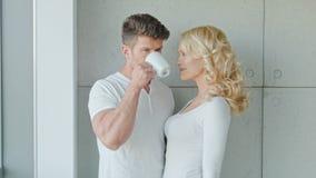 Jeunes couples heureux se tenant à côté de la fenêtre banque de vidéos