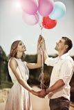 Jeunes couples heureux se tenant dans leurs ballons de mains et s colorés photographie stock