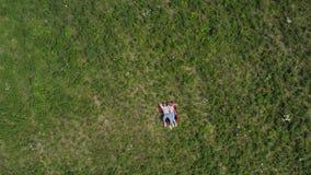 Jeunes couples heureux se trouvant sur l'herbe dans le pré L'appareil-photo vole lentement ? partir de eux Dessus aérien vers le  banque de vidéos