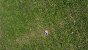 Jeunes couples heureux se trouvant sur l'herbe dans le pré La caméra pilote lentement des mouches à eux Dessus aérien vers le bas banque de vidéos