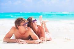 Jeunes couples heureux se trouvant sur une plage tropicale dedans Photographie stock