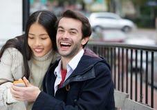 Jeunes couples heureux souriant avec le téléphone portable dans la ville Photographie stock