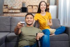 Jeunes couples heureux souriant tout en se reposant ensemble et TV de observation Photographie stock