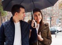 Jeunes couples heureux sous le parapluie Images stock