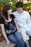 Jeunes couples heureux sur le banc de stationnement Photographie stock libre de droits