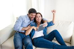 Jeunes couples heureux sur le divan à la maison appréciant à l'aide de la tablette numérique Images stock