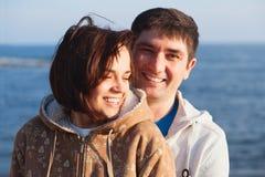 Jeunes couples heureux sur le fond de mer de coucher du soleil Images stock