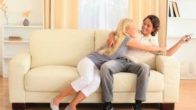 Jeunes couples heureux sur le sofa luttant pour l'extérieur banque de vidéos