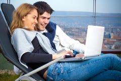 Jeunes couples heureux surfant l'Internet Image libre de droits