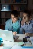 Jeunes couples heureux surfant le Web à la maison Photo libre de droits