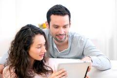 Jeunes couples heureux surfant sur un comprimé image stock