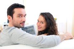 Jeunes couples heureux surfant sur un comprimé images stock