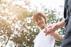 jeunes couples heureux tenant des mains dans le jardin Ami et girlfr Image libre de droits