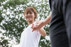 jeunes couples heureux tenant des mains dans le jardin Ami et girlfr Photo stock