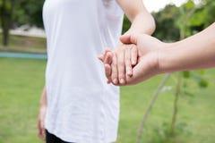 jeunes couples heureux tenant des mains dans le jardin Ami et girlfr Photographie stock libre de droits