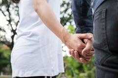 jeunes couples heureux tenant des mains dans le jardin Ami et girlfr Photos libres de droits