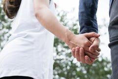 jeunes couples heureux tenant des mains dans le jardin Ami et girlfr Images stock