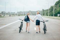 Jeunes couples heureux tenant des mains et montant sur le vélo Photographie stock libre de droits