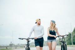Jeunes couples heureux tenant des mains et montant sur le vélo Photos stock