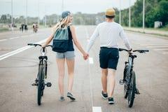 Jeunes couples heureux tenant des mains et montant sur le vélo Photos libres de droits