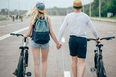 Jeunes couples heureux tenant des mains et montant sur le vélo Photographie stock