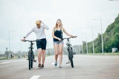 Jeunes couples heureux tenant des mains et montant sur le vélo Photo libre de droits