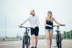 Jeunes couples heureux tenant des mains et montant sur le vélo Image libre de droits