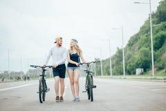 Jeunes couples heureux tenant des mains et montant sur le vélo Images stock