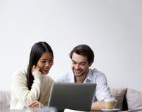 Jeunes couples heureux travaillant sur l'ordinateur portable à la maison Photos libres de droits