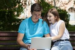 Jeunes couples heureux utilisant l'ordinateur portable se reposant sur le banc dans la ville extérieure - le concept des relation images stock