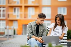 Jeunes couples heureux utilisant l'ordinateur portable se reposant sur un banc dans la ville extérieure Deux amants ayant l'amuse images stock