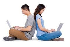 Jeunes couples heureux utilisant l'ordinateur portable tout en se reposant de nouveau au dos Photographie stock libre de droits