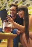 Jeunes couples heureux utilisant le comprimé dans la barre Photo stock