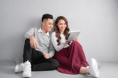 Jeunes couples heureux utilisant le comprim? se reposant sur le plancher ? la maison sur le fond gris photos stock