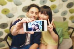 Jeunes couples heureux utilisant le smartphone dans la barre Image libre de droits